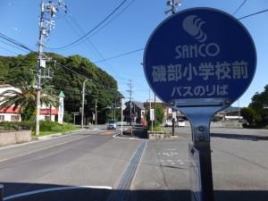 SANCO 磯部小学校前 バスのりば、前方には佐美長神社の社叢