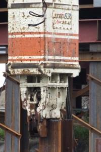 川の中に立て込まれているH鋼を噛んでいる電動式バイブロハンマー(勢田川水管橋架設工事)