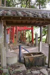 小丹神社の手水舎越しに望む宮山稲荷大明神の参道鳥居(津市上浜町)