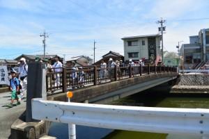 汐湯の清めに先導されて清浄坊橋を渡る「御塩道を歩く」の一行