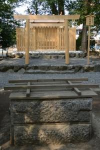 覆屋が取り外された御井越しに望む打懸神社