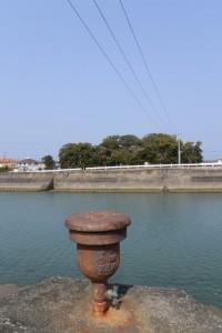 対岸から遠望する志宝屋神社の社叢と「水 1994」と陽刻された?